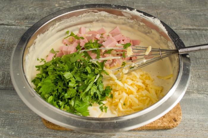 Кладём в миску с тестом колбаску, сыр и зелень