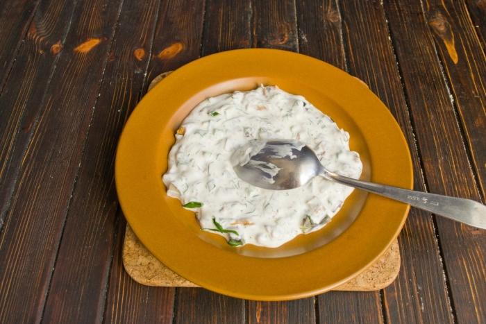 Посыпаем рубленую зелень солью, растираем и добавляем сметану