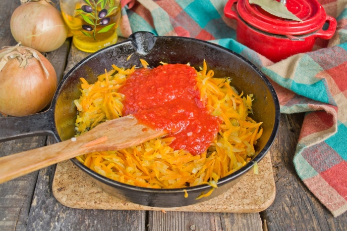 К пассерованным овощам добавляем томатное пюре, солим, перчим